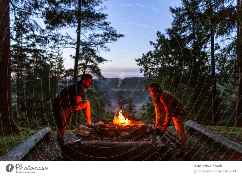 Couple with firewood making campfire in forest couple camper bonfire night log warm up friends traveler woods enjoy evening woman together relax nature love