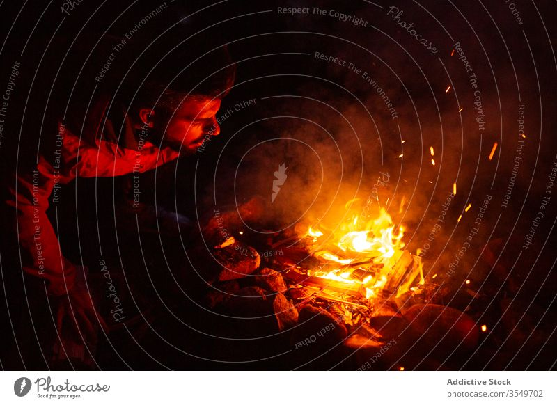 Man with firewood making campfire in forest man camper bonfire night log warm up male calm traveler tranquil woods enjoy weekend evening relax nature chill