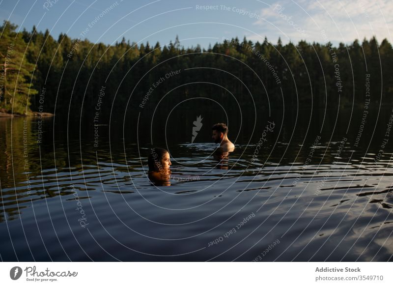 Man and woman swimming in forest lake in summer couple travel nature together trip relax sun harmony daytime weekend calm clean sunny vacation leisure water