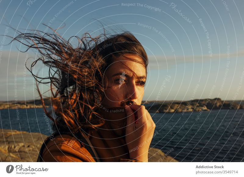 Thoughtful young female tourist standing on rocky seashore and looking away woman traveler harmony dream pensive wave hair wind nature coast vacation thoughtful
