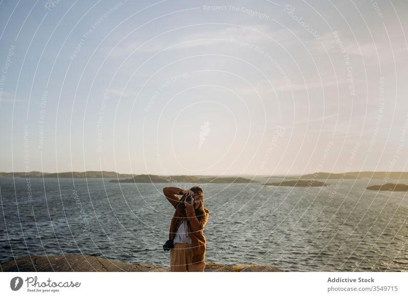 Anonymous female tourist standing on rocky seashore and taking photos woman take photo cliff coastline seascape nature journey photo camera tourism vacation