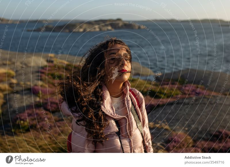 Young woman standing near lake shore breeze enjoy sunny female calm tranquil serene wind wavy hair relax vacation holiday rest water river pensive thoughtful