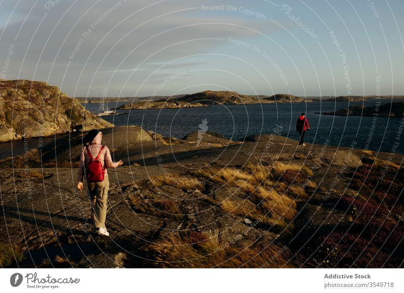 Anonymous couple of tourists walking on rocky seashore together seascape outerwear vacation nature travel adventure tourism relationship journey landscape