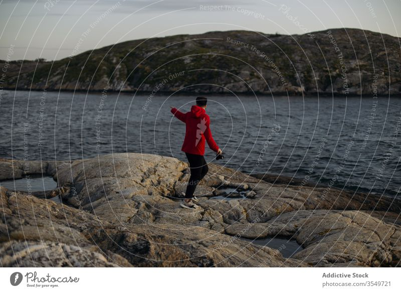 Male tourist with photo camera standing on rocky lake shore man travel contemplate hill lakeside cloudy sky river stone explore vacation tourism weekend casual