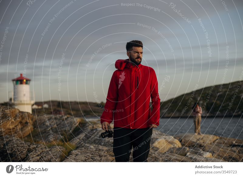 Male tourist with photo camera standing on rocky lake shore observation tower travel contemplate hill lakeside cloudy sky river stone explore vacation tourism