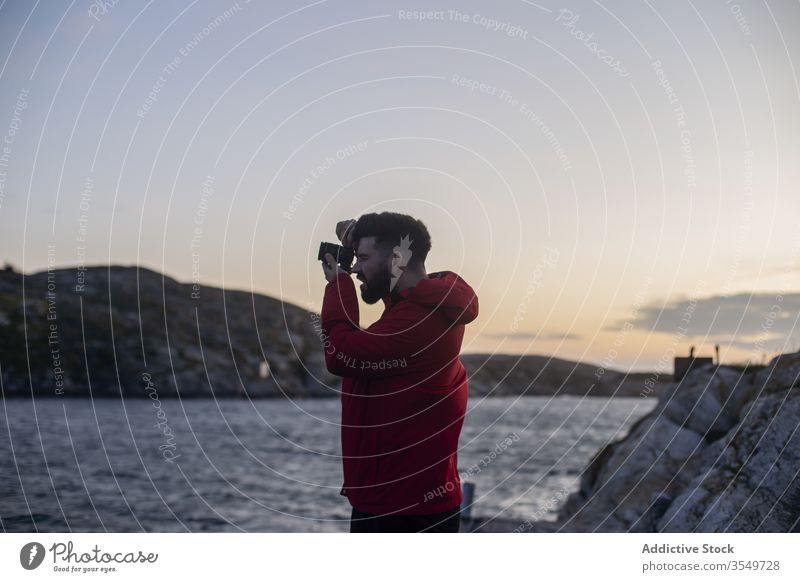 Man taking picture on photo camera on sea shore man take photo rocky photographer coast cliff sundown evening nature trip travel hoodie wanderlust adventure