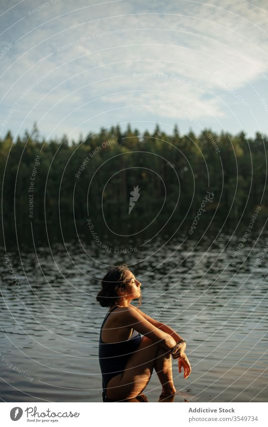 Woman in swimsuit sitting in lake woman water calm sunset enjoy summer majestic scenery female forest landscape tranquil serene harmony peaceful idyllic wood