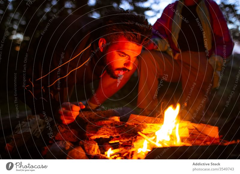Man with firewood making campfire in forest man camper bonfire night log warm up male calm traveler tranquil woods enjoy weekend evening trees relax nature