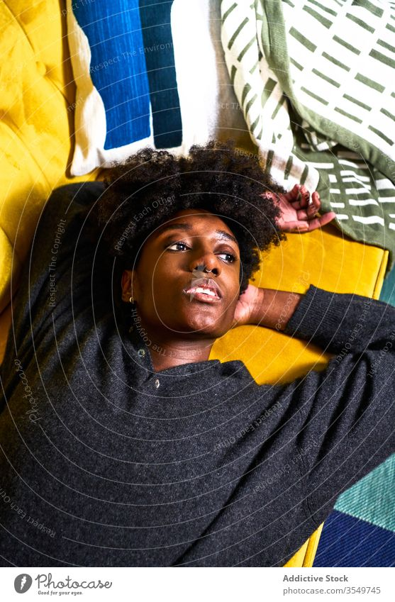 Young black woman resting on colorful sofa home lying bored pensive design thoughtful dream young african american female casual couch ethnic isolation relax