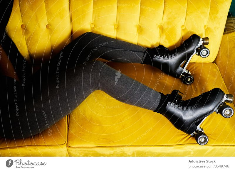 Anonymous woman in roller skates lying on sofa stay home activity colorful young black female african american concept relax restriction coronavirus isolation