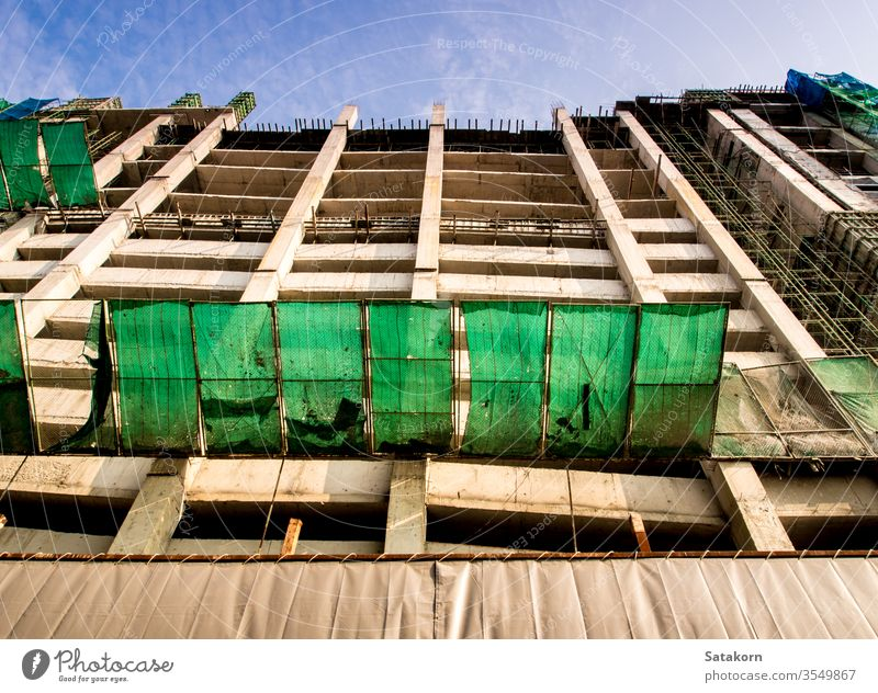 The high-rise building under construction concrete sky blue engineering structure development site scaffolding steel work city urban business industry