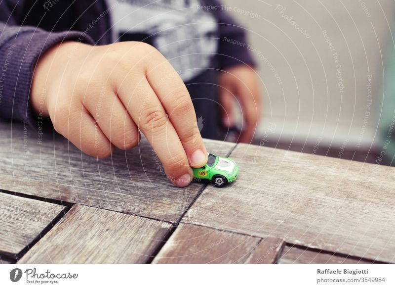 my son is playing with his favourite car , the micro machine that it belonged to me , an evergreen smile home lovely baby playful happiness imagination park