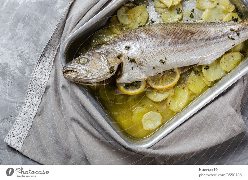 Fresh raw sea bass fish prepared for roasting with potatoes roasted food fresh seafood corvina sea basses background healthy lemon thyme ingredient cooking