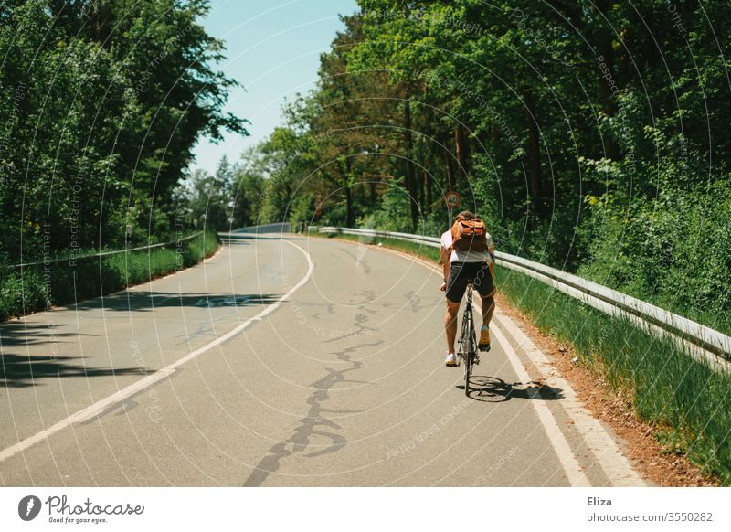 A man rides uphill on a bicycle on the road. Riding a bike. Trip. Cycling Summer Driving Bicycle out Sun hillock Incline Tall Sports Nature Man Street Lifestyle