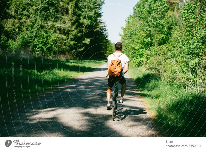 A cyclist on a path through the forest on a bike trip Bicycle Man Trip Nature Cycling tour Summer sunny Backpack T-shirt Dark-haired huts off spring