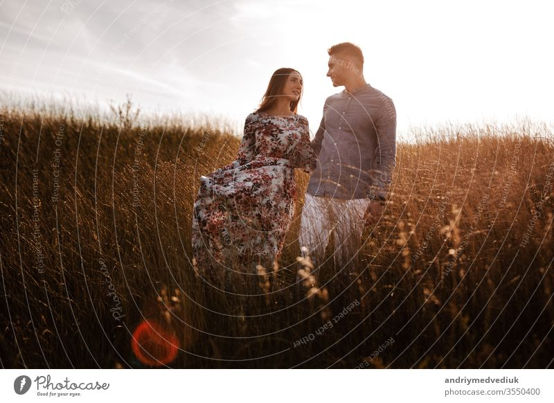 young couple resting in nature in a field. couple at sunset summer relationship man romantic love lifestyle landscape happy happiness people portrait girl
