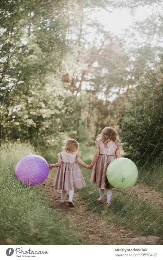 two beautiful little girls in the summer in a park with balloons in hands. Happy girl with balloons. kids children freedom family happy playing holding running