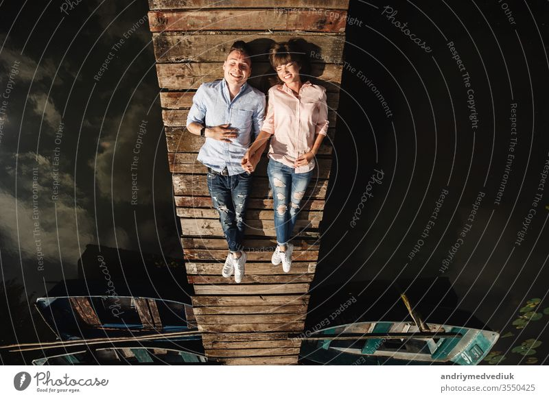 Beautiful young couple lies on a wooden bridge on the lake, looks lovingly at each other and smiles. Love story. beautiful people together lifestyle family