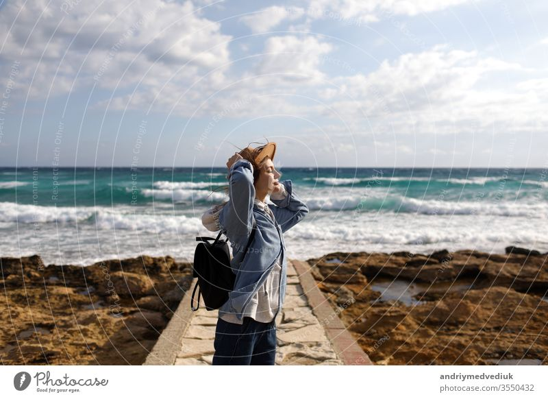 female traveler admiring a marine view. tourism in Cyprus. tourist on sea background. girl travels on the beaches. young beautiful hipster woman on tropical beach, summer vacation, happy, fun,