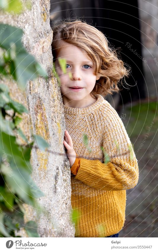 Happy blond child with long hair outside boy childhood tree hide park kid cute white happy portrait little caucasian people young smile happiness fun casual