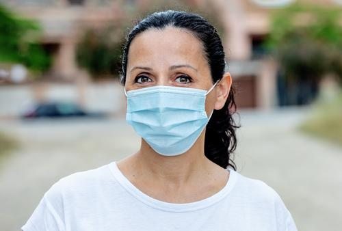 Brunette woman wearing a mask protection street face outdoor corona healthcare Covid-19 coronavirus influenza city pandemic girl medical epidemic people