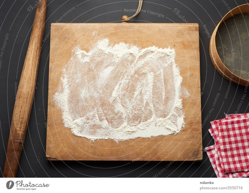 white wheat flour scattered on a black table and a wooden rolling pin dough food fresh freshness grain home bake abstract background bakery board bread brown