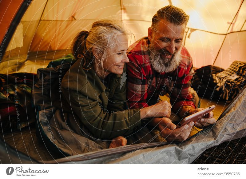 Happy senior couple using phone inside tent on camping trip smartphone technology smile connected internet browsing online happy enjoying active activity