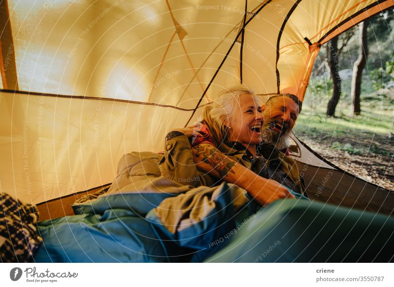 Senior couple laughing and cuddling inside tent in bedroll laying down smile happy enjoying active activity tourist leisure holiday seniors travel backpack