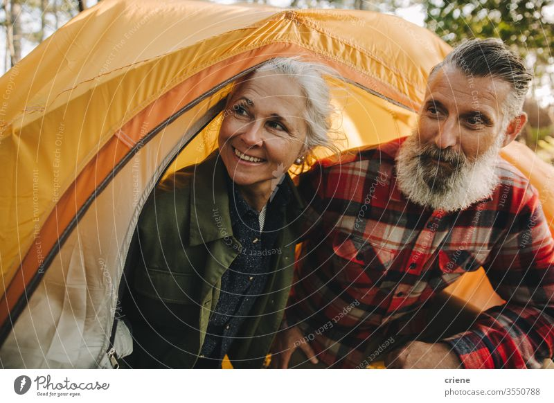 Happy senior couple looking outside yellow tent smiling smile happy enjoying active activity tourist leisure holiday seniors travel backpack nature hiking love