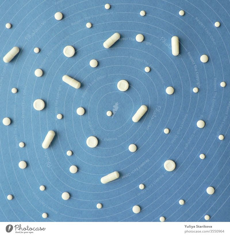 Creative scandinavian style flat lay top view of white pills and capsules on a blue background. Treatment and of hope for recovery. Creative idea for drugstore, online pharmacy, health lifestyle and pharmaceutical company business concept.