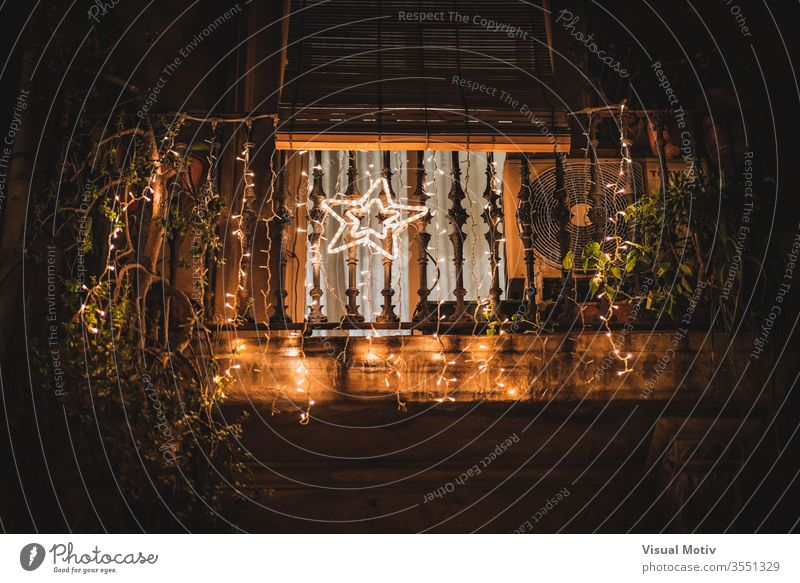 A light star hanging on a balcony decorated with light garlands at night illuminate branch shine tree house evening dark holiday festive glow celebrate