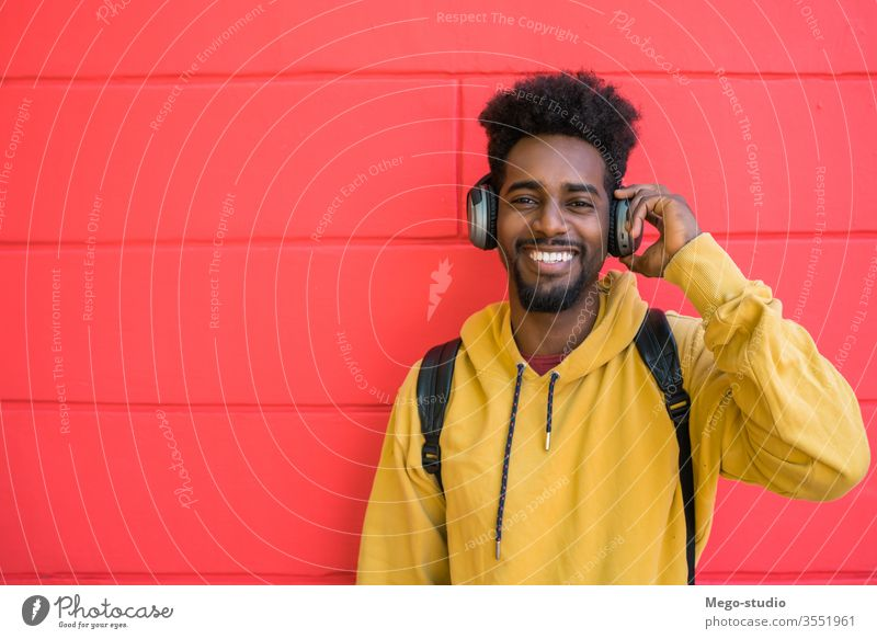 Young afro man listening to music with headphones. earphones happy sound background adult modern young friendly media expression cool in-ear earbud portable