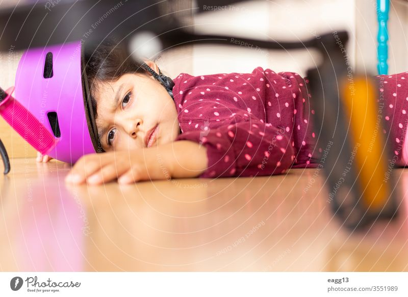 Sad little girl fell to the ground while playing with her bicycle in the house accident accidental ache aid at home bicyclist bike biker biking care child crash