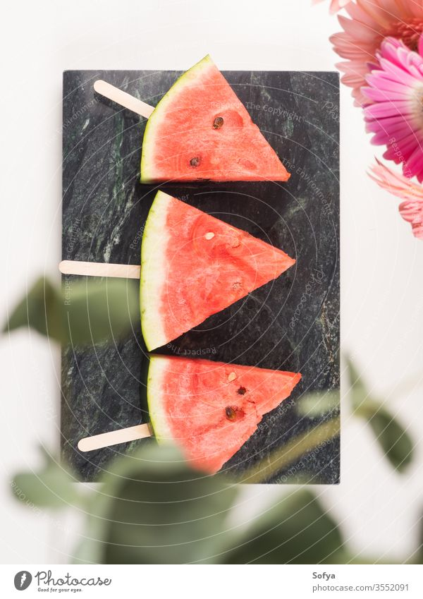 Watermelon slice popsicles on marble tray watermelon summer slices pink white wooden table fresh snack berries flowers delicious beautiful bright eat food sweet