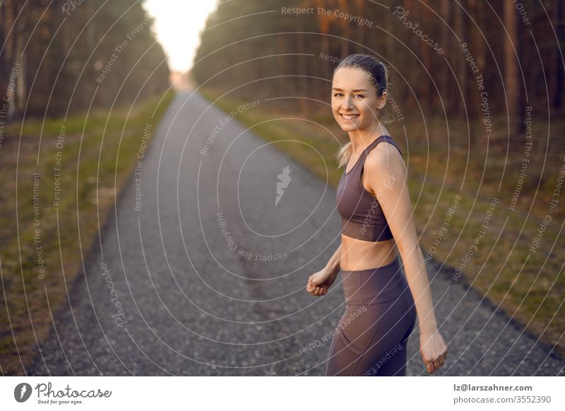 Fit athletic young woman out jogging at sunrise along a straight receding road through forest trees with glow of the sun at the end turning to smile at the camera in a healthy active lifestyle concept