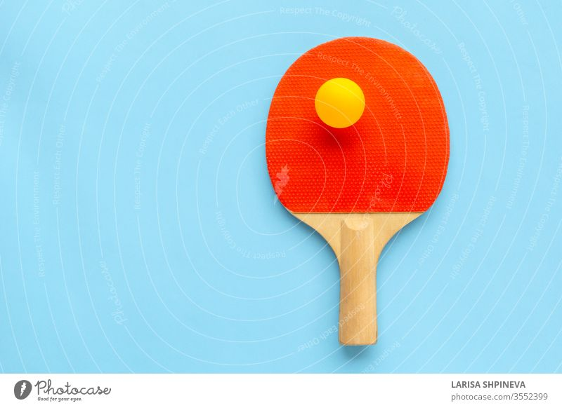 Red racket for table tennis with yellow ball on blue background. Ping pong sports equipment in minimal style. Flat lay, top view, copy space ping handle game