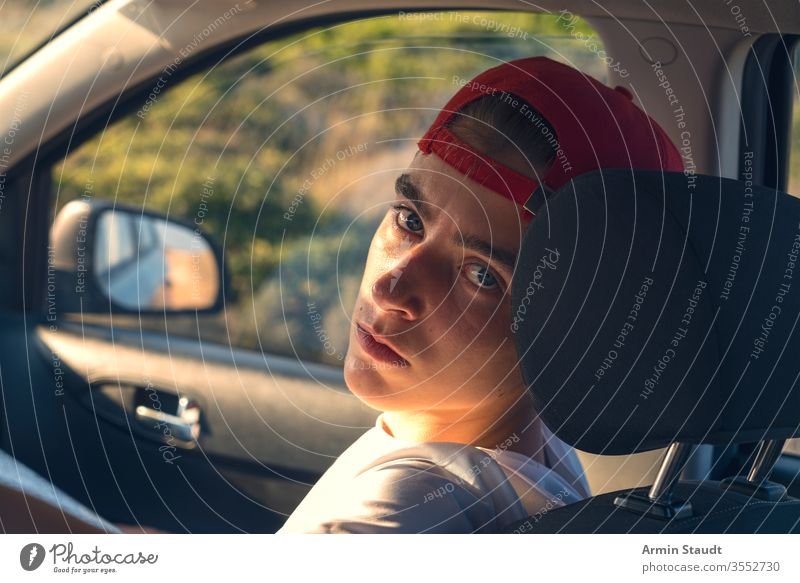 Portrait of a young man sitting in a car Baseball cap already Boy (child) Car Easygoing Caucasian Self-confident Driving voyage Lifestyle Looking Manly Model