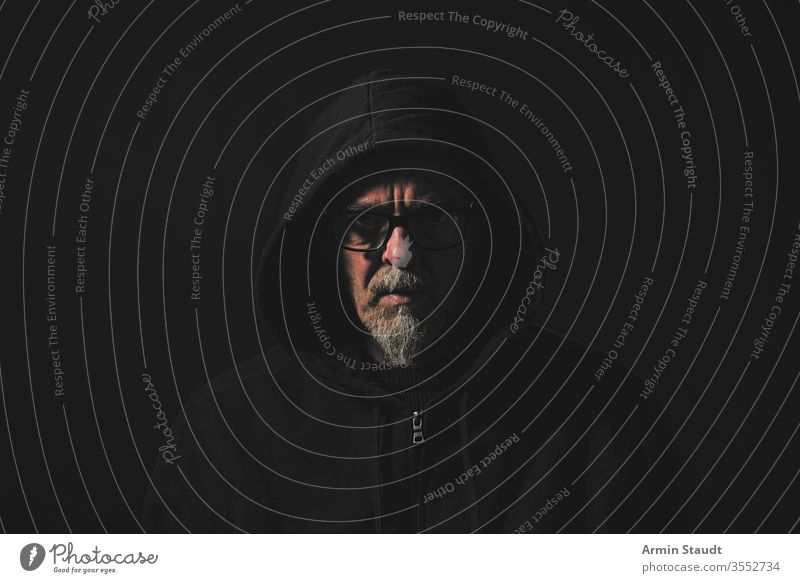 dark portrait of a man with gray beard , hoodie and glasses angle black blur casual caucasian close-up closeup confident cool danger dramatic emotion expression