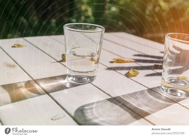 two glasses on a table with autumn leaves aqua background beverage clean clear closeup cool drink empty exterior flare fresh freshness half-full hand light