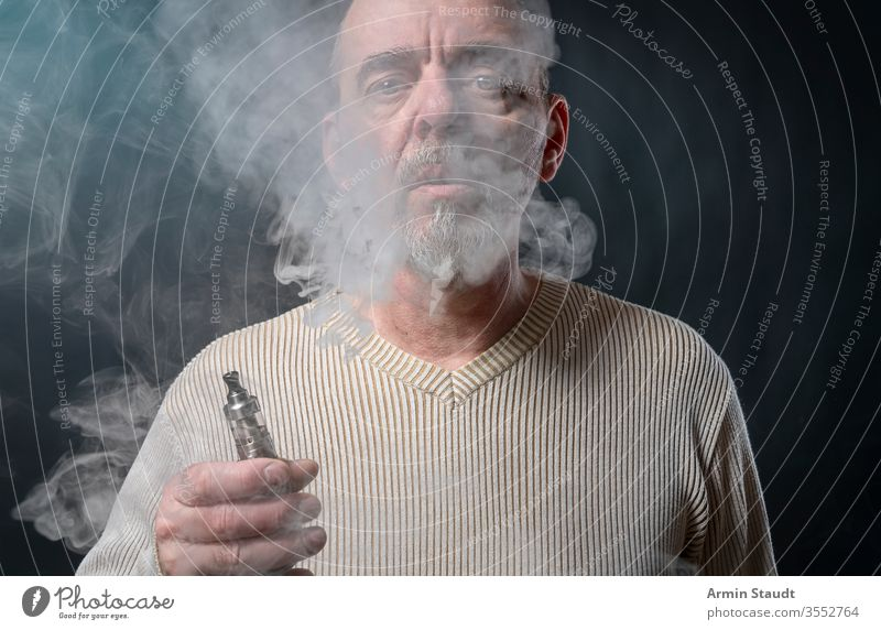 portrait of a man with beard who is vaping background blowing blur cigarette cigarettes cool e-cigarette ecig electronic equipment exhaling gray hand health