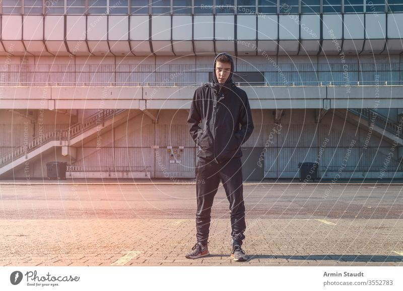 portrait of a young man with black hoodie adolescent architecture beautiful boy building casual caucasian confident eager lifestyle looking male model outdoor