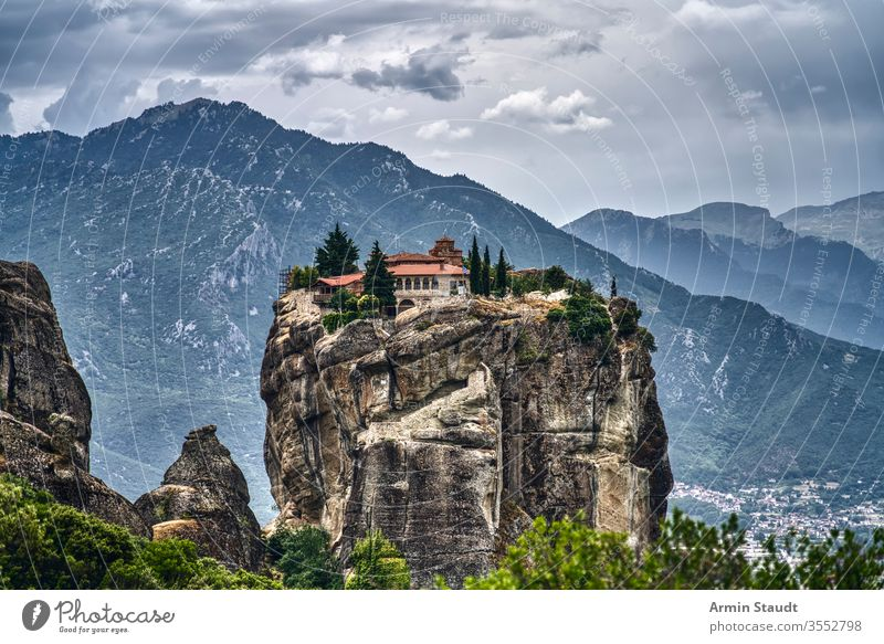 Monastery on a huge rock in Meteora, Greece with mountain range and dramatic clouds meteora monastery abbey church cliff culture architecture attraction