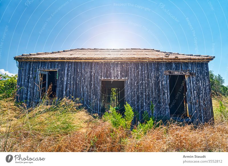 old abandoned wooden cottage with the sun behind damaged empty idyllic greece nature countryside architecture barn blue broken building corrugated environment