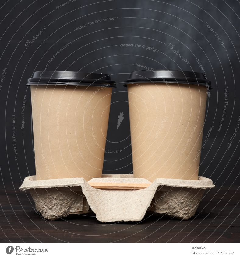 two brown paper disposable cups with a plastic lid stand in the tray on a wooden table container cover drink empty americano background beverage black blank