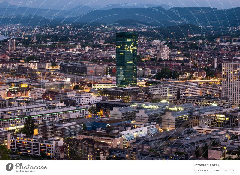 Zurich city Switzerland view with famous skyscraper vista point in the evening blue hour evening after sunset cloudy sky detail city lights dark panoramic swiss