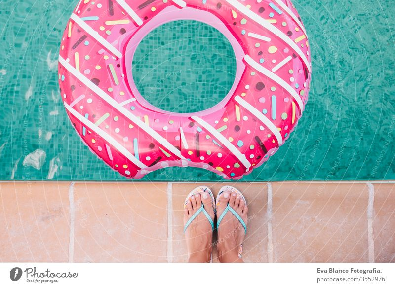 top view of a woman feet flat lay. Woman relaxing in the pool with pink donuts in hot sunny day. Summer holiday idyllic. Enjoying suntan Woman in bikini on the inflatable in the swimming pool.