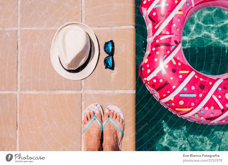 top view of a woman feet flat lay with hat and sunglasses. Woman relaxing in the pool with pink donuts in hot sunny day. Summer holiday idyllic. Holidays concept