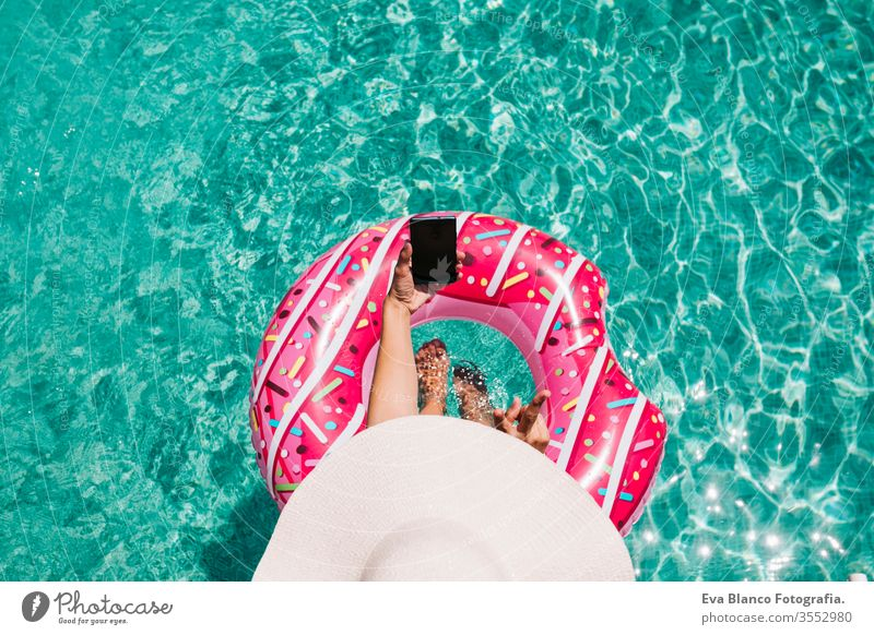 top view of a woman relaxing in the pool with pink donuts in hot sunny day. Summer holiday idyllic. Enjoying suntan Woman in bikini and a hat. Holidays and summer lifestyle. She is using mobile phone