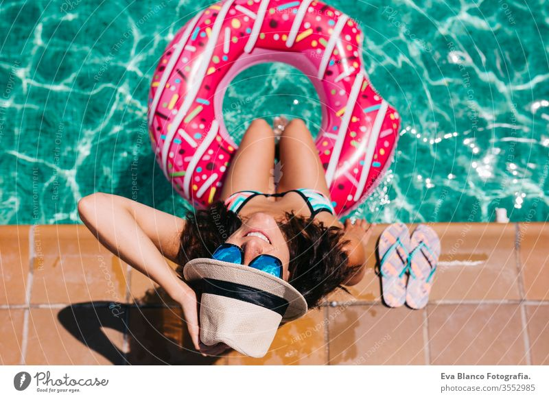 top view of a woman relaxing in the pool with pink donuts in hot sunny day. Summer holiday idyllic. Enjoying suntan Woman in bikini and a hat. Holidays and summer lifestyle