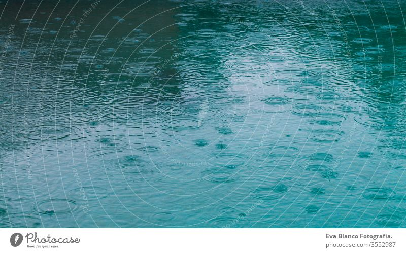 Round droplets of water over the circles on the water. Water rain drop, whirl and splash. Ripples on pool texture pattern background. Desktop or laptop wallpaper. Closeup water rings affect the surface.
